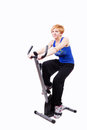Woman doing sports on exercise bike Stock Photos