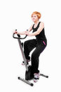 Woman doing sports on exercise bike Royalty Free Stock Photography