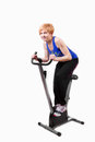 Woman doing sports on exercise bike Stock Photography