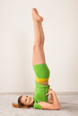 Woman doing stretching exercises on yoga sarvangasana shoulder stand pose by young beautiful Royalty Free Stock Image