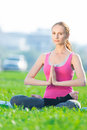 Woman doing stretching fitness exercise yoga lotus beautiful sport in city park at green grass pose Stock Photography