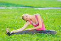 Woman doing stretching fitness exercise yoga postures beautiful sport in city park at green grass Stock Photography