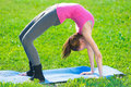 Woman doing stretching fitness exercise yoga postures beautiful sport in city park at green grass Stock Photos