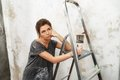 Woman doing wall painting disgruntled young brunette with ladder and brush Royalty Free Stock Photos