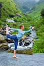 Woman doing yoga asana Natarajasana outdoors at waterfall Royalty Free Stock Photo