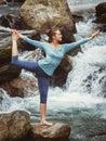Woman doing yoga asana Natarajasana outdoors at waterfall Royalty Free Stock Photo