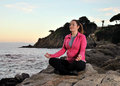 Woman doing yoga exercise from the sea Royalty Free Stock Image