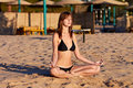Woman doing yoga meditation in lotus on the beach Stock Photos