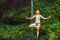Woman Doing Yoga near Tropical Waterfall Stock Photo