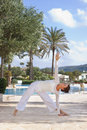 Woman doing yoga next to pool middle aged warrior pose with eyes clothes Royalty Free Stock Photography