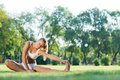 Woman doing yoga in the park young attractive active lifestyle Stock Image