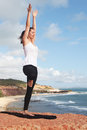 Woman doing the yoga tree exercise on sea coast Stock Photography