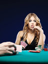 Woman doubt in a card gambling match Stock Photography