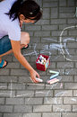 Woman drawing with chalks overhead view of picture on pavement or sidewalk Stock Image