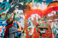 Woman draws on the John Lennon Wall in Prague