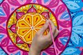 Woman draws a mandala, hand with a brush close-up