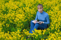 Woman draws sitting on a grass in the daytime. She paints sitting on a rapeseed field.