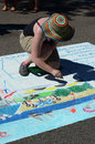 Woman draws on the street with chalk a uses and pastel drawing this is part of st joseph michigan s block event Stock Image