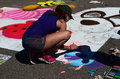 Woman draws on the street a uses chalk and pastel drawing this is part of st joseph michigan s chalk block event Royalty Free Stock Images