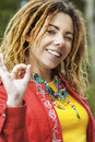 Woman with dreadlocks making sign all ok young smiling beautiful in red clothes of fingers Stock Image