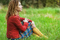 Woman with dreadlocks sits grass young sad beautiful in a red dress on green in park Stock Photography