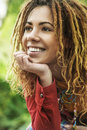 Woman with dreadlocks sitting on bench young smiling beautiful in red dress wooden Stock Photos