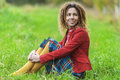 Woman with dreadlocks sitting on grass young smiling beautiful in red clothes in park Royalty Free Stock Photos