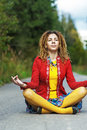 Woman with dreadlocks sitting in lotus position young beautiful red clothes on pavement and laughs Stock Photo