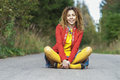 Woman with dreadlocks sitting in lotus position young beautiful red clothes on pavement and laughs Royalty Free Stock Images