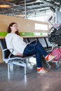 Woman dreaming with tablet pc in airport lounge luggage hand cart Stock Photo