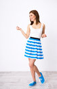Woman in dress with follow me gesure full length portrait of a smiling Royalty Free Stock Image