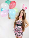 Woman dressed bunny ears holds balloons Stock Photos