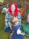 Woman dressed in costume of celtic period with dyed red hair taking part through the centuries entertainment and reenactment at Stock Image
