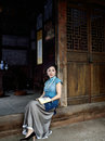 A woman dressed in traditional chinese costume sitting on the threshold of the old house Stock Image
