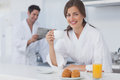 Woman with a dressing gown having breakfast while her husband is reading newspaper on the background Stock Photo