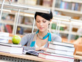 Woman drills at the reading hall with green apple surrounded with piles of books reads sitting table library information overload Royalty Free Stock Image