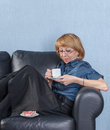 Woman drink coffee on couch Stock Photography