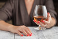 Woman drinking alcohol on dark background. Focus on wine glass Royalty Free Stock Photo