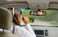 Woman drinking alcohol and driving view from behind inside a car of driver drink lifting the bottle to her lips gulping down the Stock Image