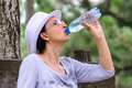Woman drinking bottled water outdoor sitting on wooden bench white hat and glasses summer time warm Royalty Free Stock Image