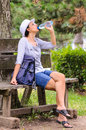 Woman drinking bottled water outdoor sitting on wooden bench white hat and glasses summer time warm Stock Photography