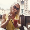 Woman drinking cocktail in front of St Mary`s church in Krakow. Poland.
