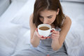 Woman drinking coffee on the bed Royalty Free Stock Photo
