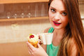 Woman drinking coffee and eating delicious cake gourmet sweet cream glutton girl sitting in kitchen with hot beverage cupcake Stock Images