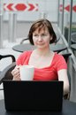 Woman drinking coffee in a outdoor cafe and using laptop Stock Images