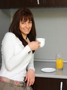 Woman drinking coffee smiling beautiful in kitchen with glass of orange fresh juice Royalty Free Stock Image