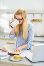 Woman drinking coffee while studying in kitchen young Royalty Free Stock Image
