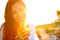 Woman drinking coffee in sunshine sitting outdoor sun light enjoying her morning smiling happy multiracial female asian Royalty Free Stock Images