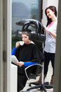 Woman drinking coffee tea in hair beauty salon by hairdresser young women hairdressing girl dying colouring hairstylist modern Stock Image
