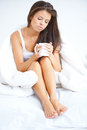 Woman drinking a cup of coffee in bed Royalty Free Stock Photo